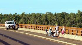 歩道橋から釣りをする人々